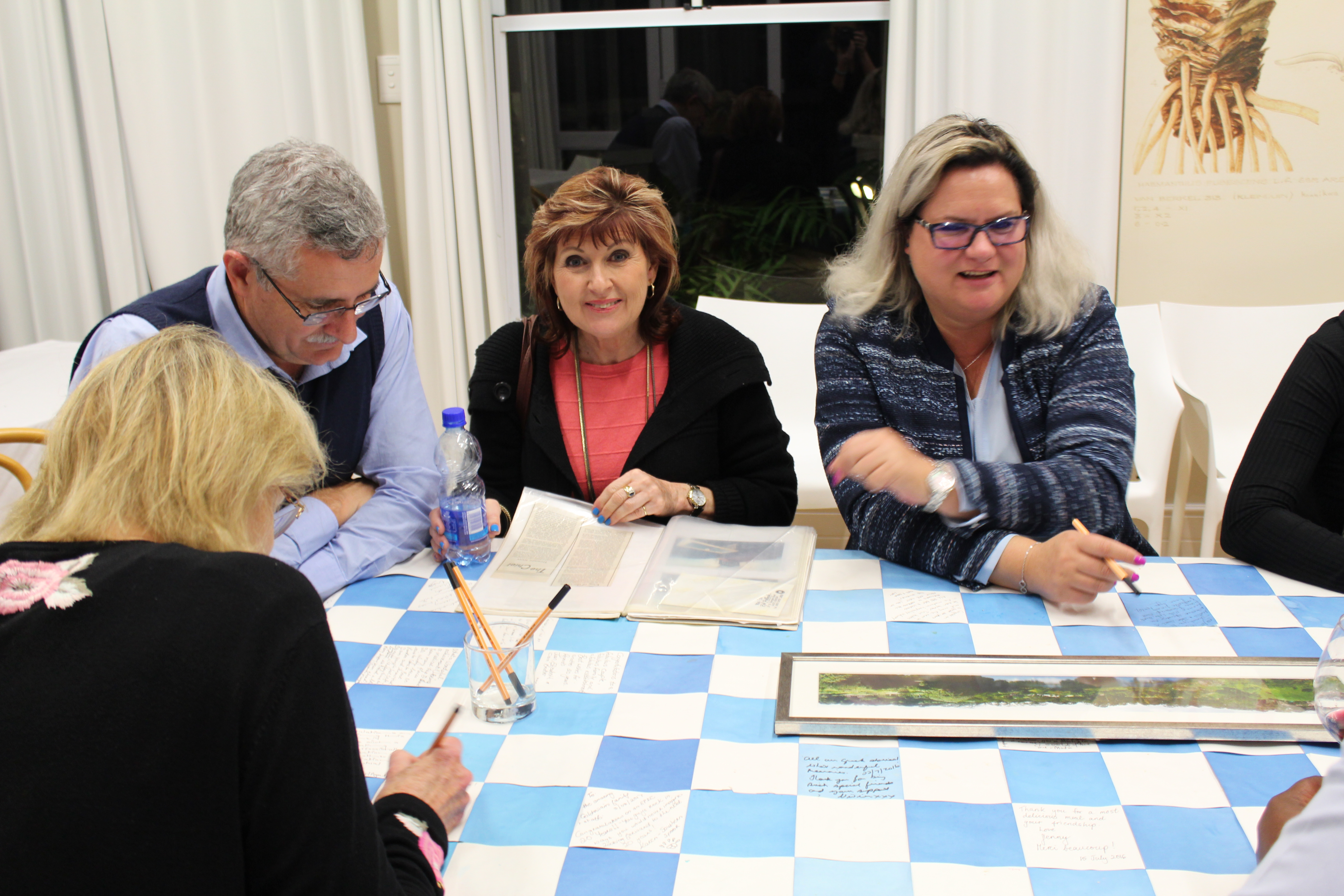 Guests signing the handmade paper tablecloth to commemorate the 20th birthday of Quarry Lake Inn.